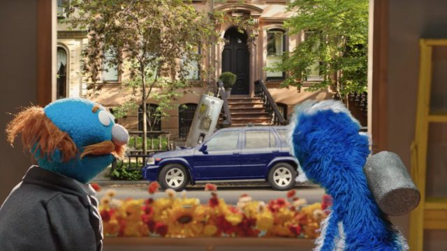 Muppets look out a window at a blue car