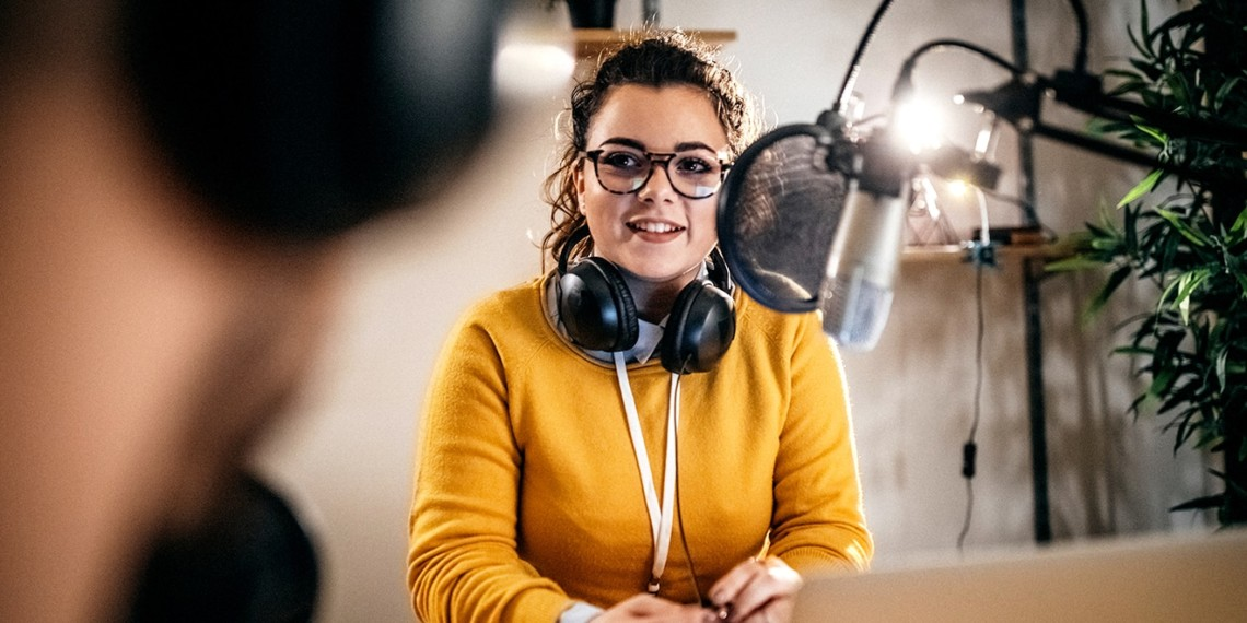 a young woman records a podcast into a microphone