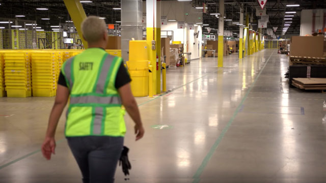 A person in a yellow vest walks in a warehouse.