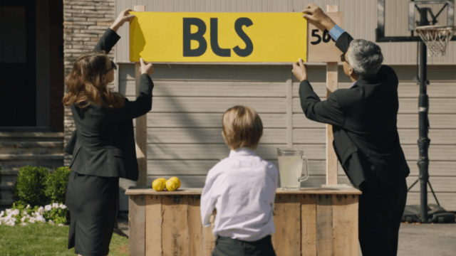 Two adults in black suits put a new sign on a child's lemonade stand.