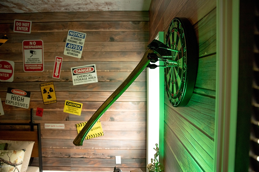 Ax sticking out of a dart board with caution signs on the wall behind it