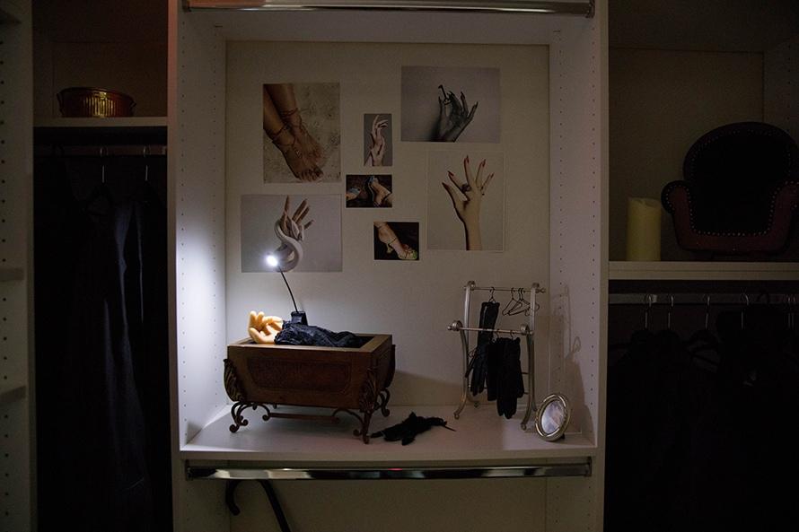 A fake hand sits in a box in a closet.