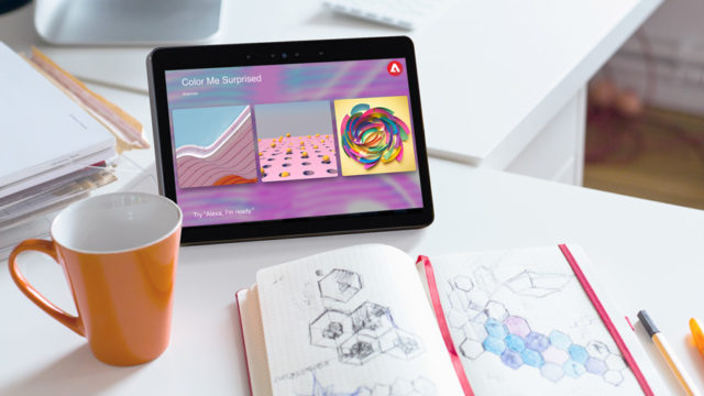 A tablet open with an Adobe app, a cup and a notebook open to a page of doodles
