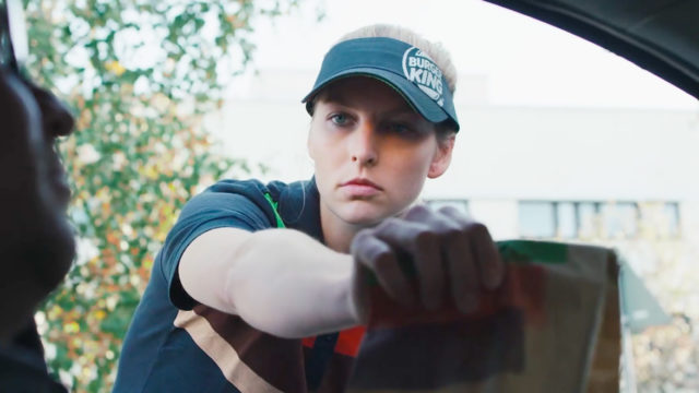 A stoic female Burger King employee hands a delivery to a driver