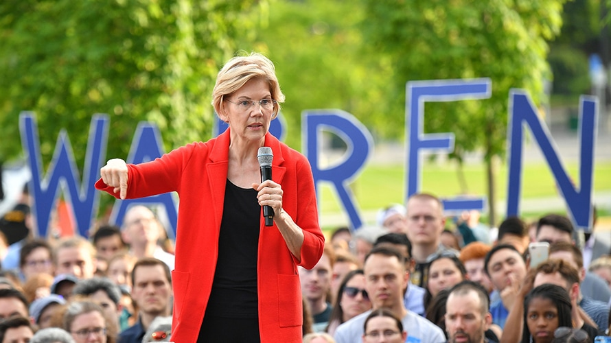 Elizabeth Warren in red jacket speaking in front of a rally outdoors