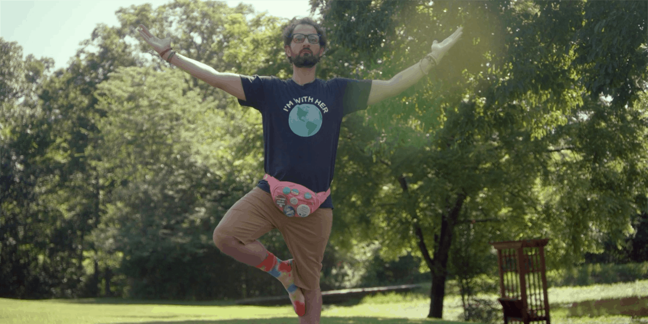man doing a yoga pose in a park