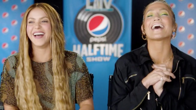 Shakira and Jennifer Lopez sitting side by side laughing