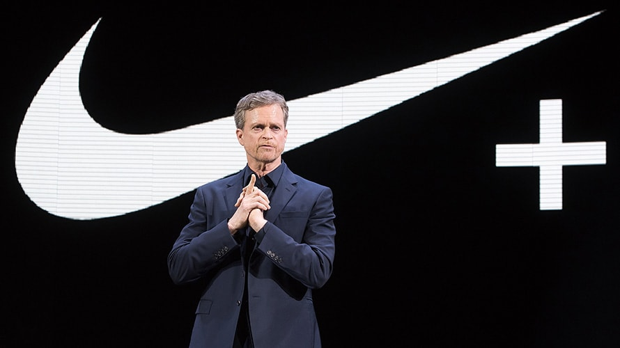 photo of man in front of Nike Just Do It checkmark logo