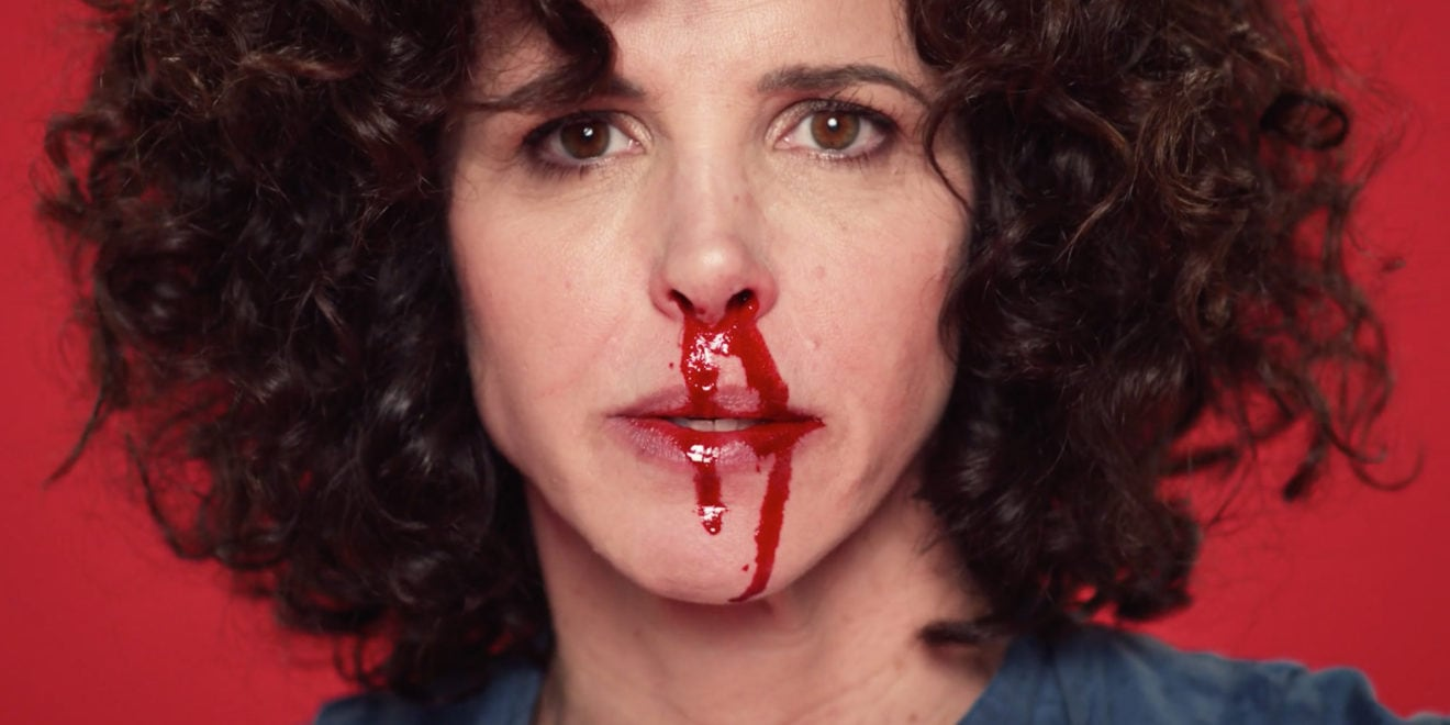 a woman with lots of curly hair having a nosebleed