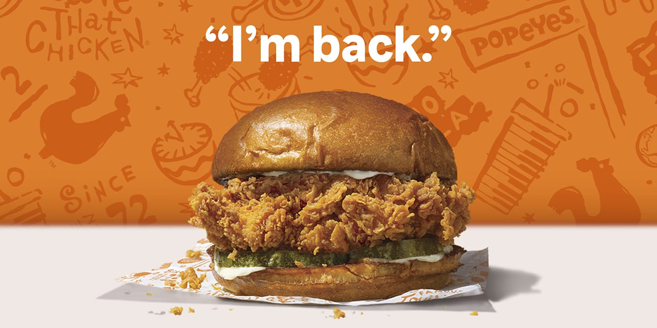 The Popeyes Chicken Sandwich sits on a wrapper under the words I'm Back