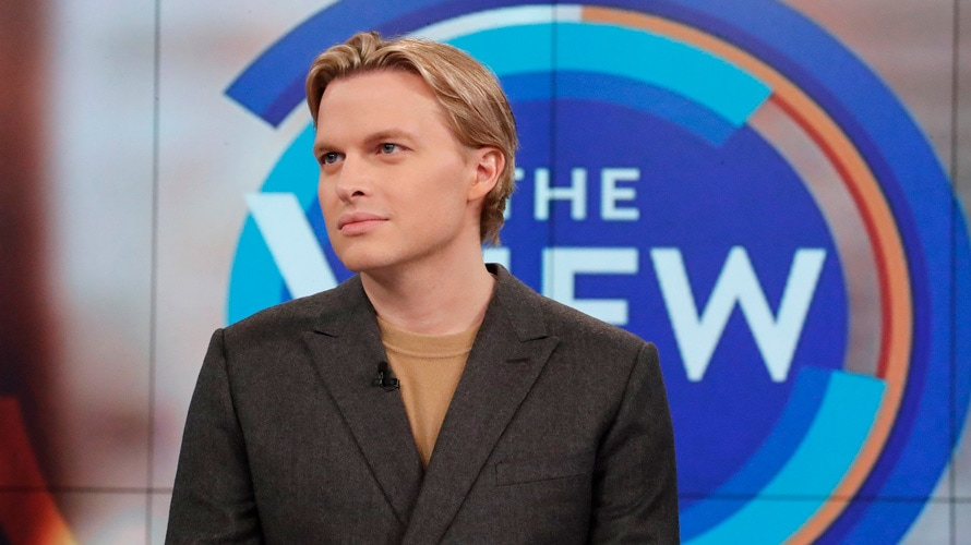 ronan farrow in front of a sign for the view