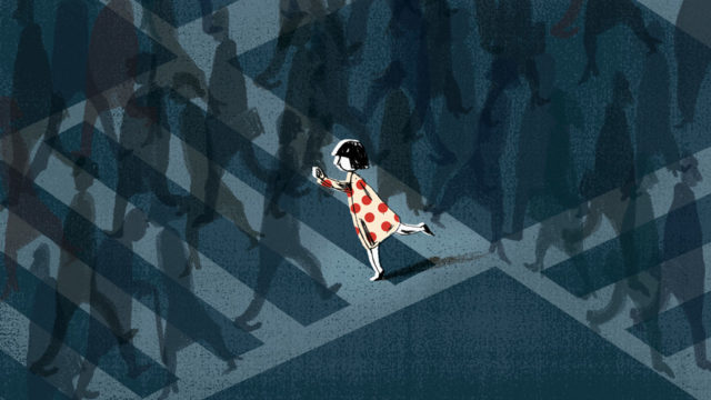 A person in a red polka dot dress standing out on a sidewalk full of people