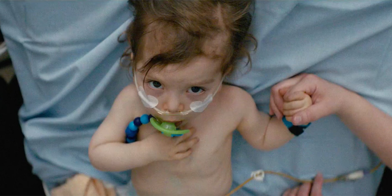 A toddler with a pacifier lies in a hospital bed and holds hands with an adult