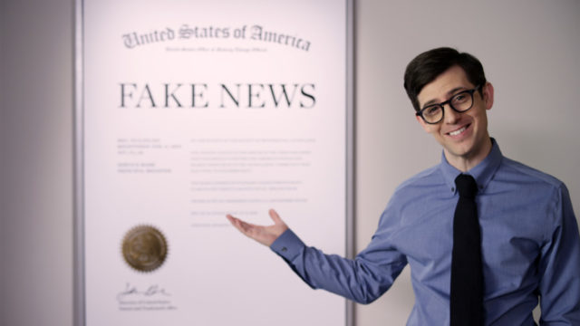 man in a tie standing in front of a fake news trademark certificate