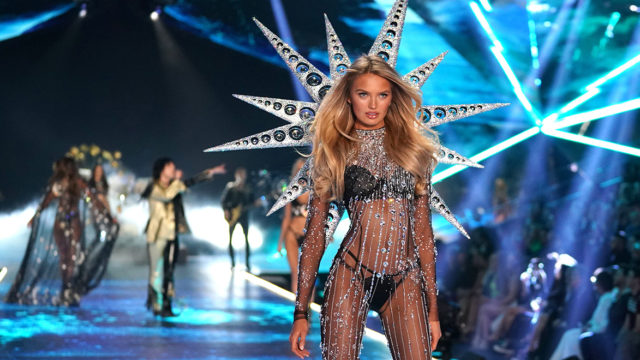 "model with long blonde hair (Romee Strijd) walks the runway at the Victoria's Secret 2018 fashion show wearing strings of crystals and spiked ""wings"""
