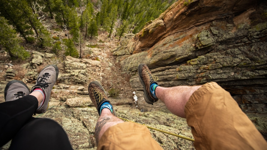 two people dangling their feet off a rocky ledge