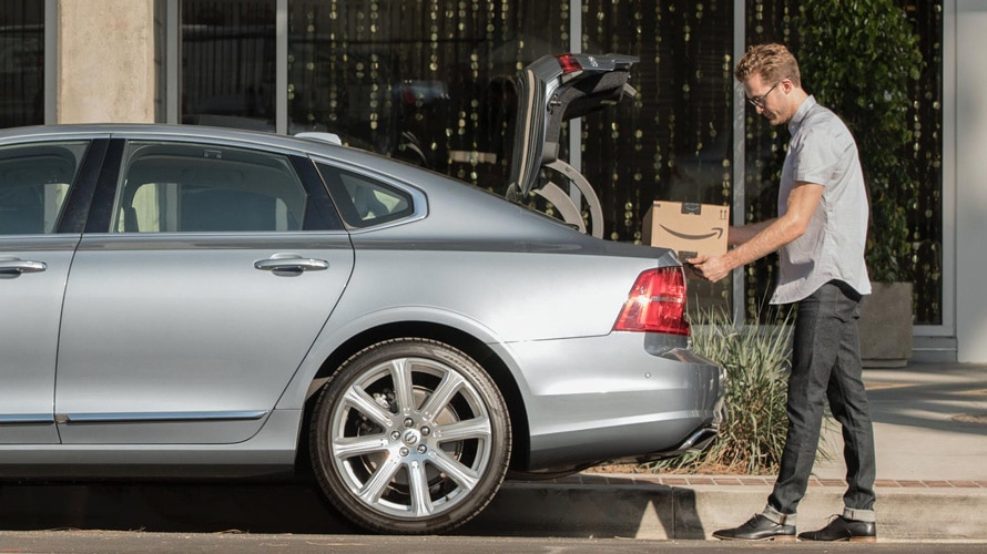 A man taking an Amazon package out of the back of his car