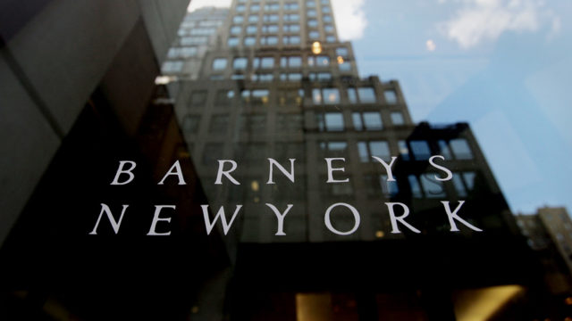 Barneys New York logo and a reflection of a building