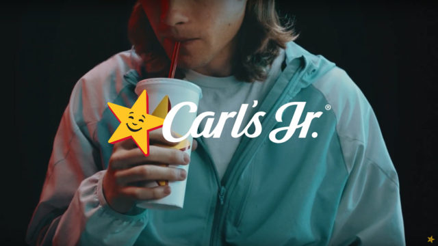 Person drinking from Carl's Jr. cup; Carl's Jr logo
