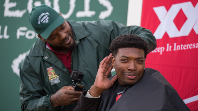 Football star Martellus Bennett cutting hair at the Dos Equis College Football Football College Bowl Game