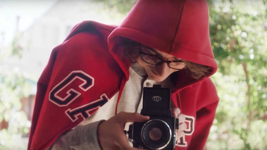 Teenage male wearing a red gap hoodie taking a picture with an old camera