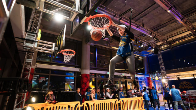 a person making a basketball dunk at hooptopia