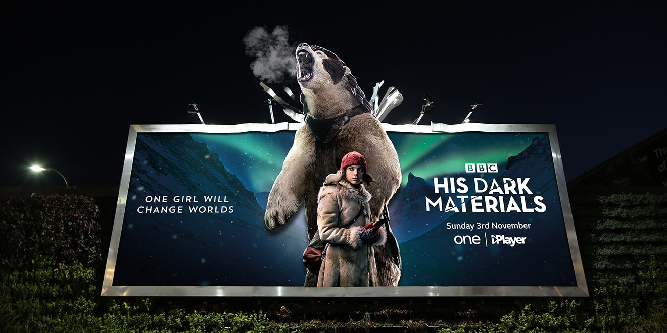 A billboard ad for His Dark Materials shows protagonist Lyra and an armored polar bear who appears to breathe
