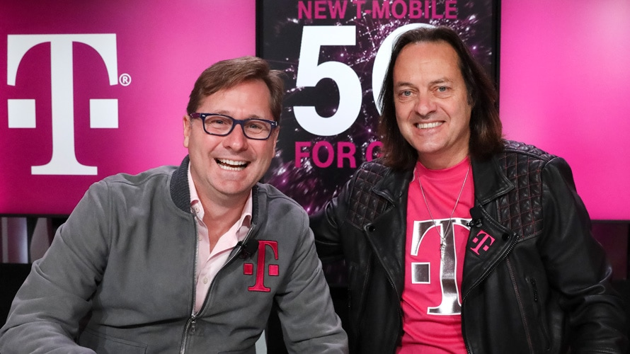 T-Mobile's Mike Sievert and John Legere sitting next to each other smiling wearing T-Mobile clothing
