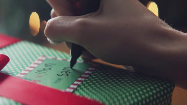 "A closeup of a hand writing ""Sam"" on a gift that says, ""To Mom."""