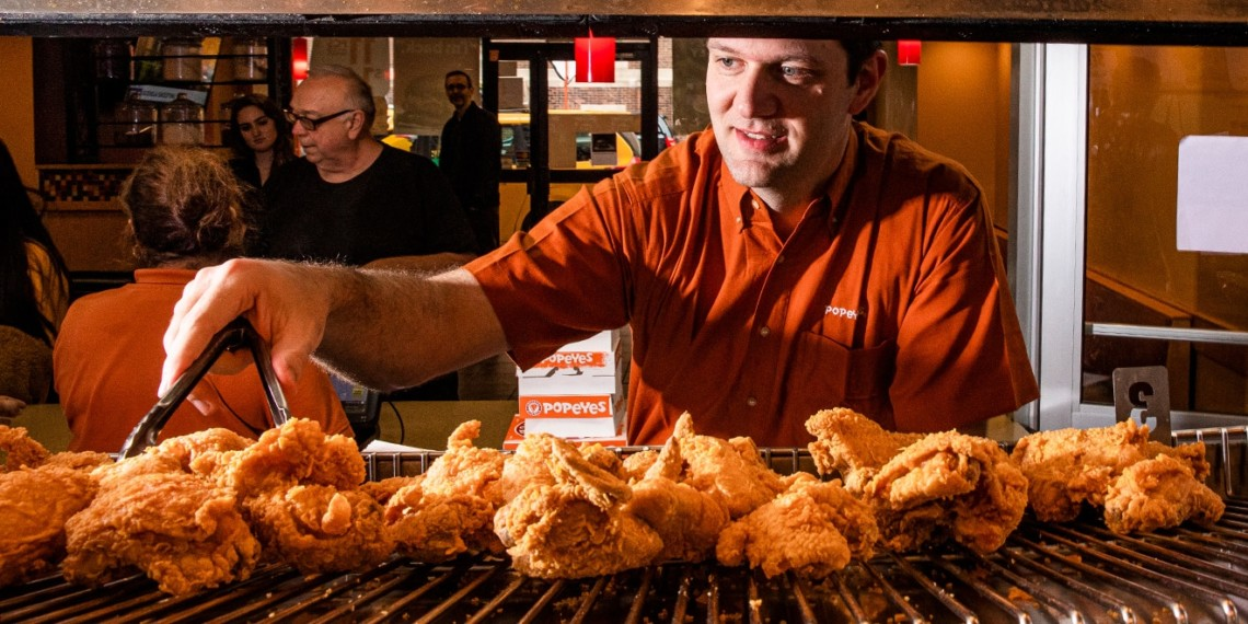 Popeyes' head of North American marketing, Bruno Cardinali, picking out a piece of chicken with tongs