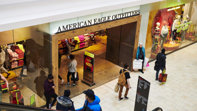 People walking by, in, and out of American Eagle store at a mall