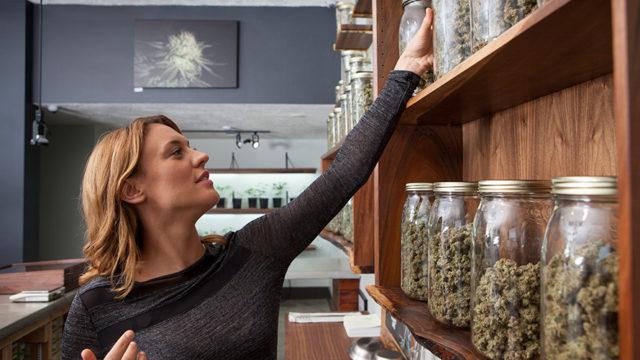 a woman at a marijuana dispensary reaching for a jar