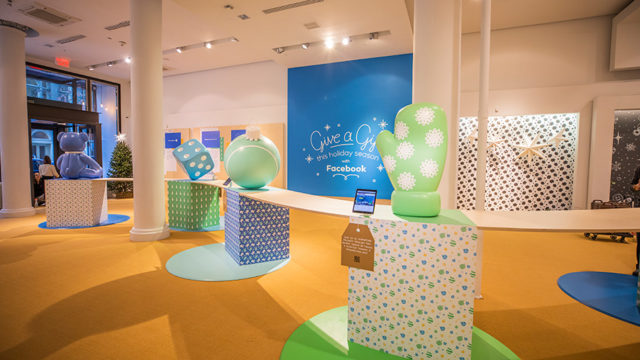 a room with pedestals holding giant mittens and electronic boards inviting people to donate