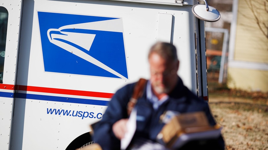 USPS mailman in the foreground and USPS truck in the background