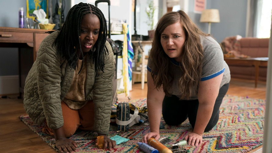 Lolly Adefope and Aidy Bryant in Shrill. Fran, a Black woman in her late twenties, and Annie, a white woman in her early thirties, are on their hands and knees on the floor of their apartment, as if looking for something. Fran has her hair in small braids, and wears an olive green patterned jacket over a beige t-shirt and orange pants. Annie is wearing a grey t-shirt with blue hems on the sleeves, and black pants. The apartment in the background is bright and fun with modern, colourful furnishing.