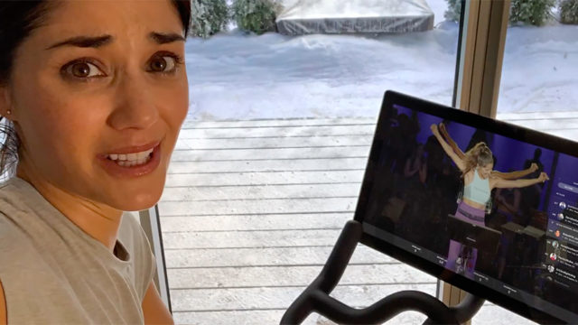 A woman rides a Peloton bike and records video of herself while looking at the camera