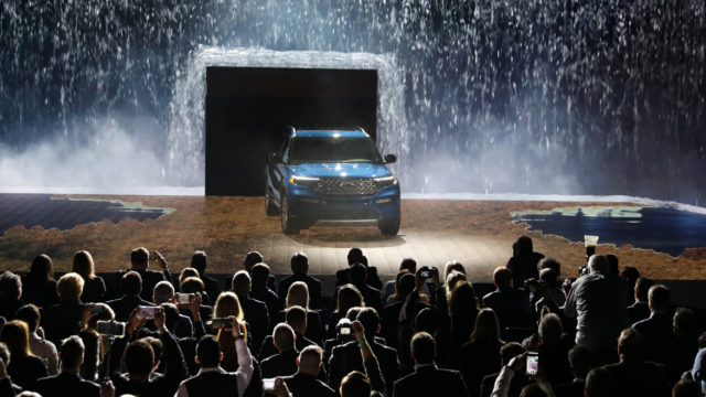 an suv onstage coming through a wall of water