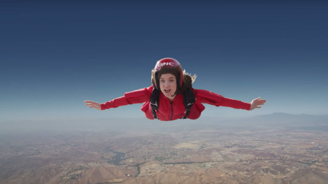 woman skydiving in a red jumpsuit and gnc helmet