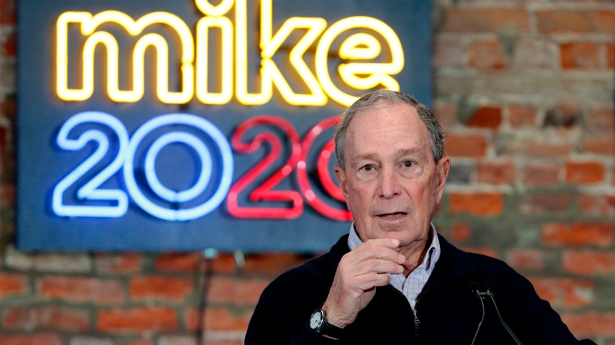 michael bloomberg in front of a sign that says Mike 2020