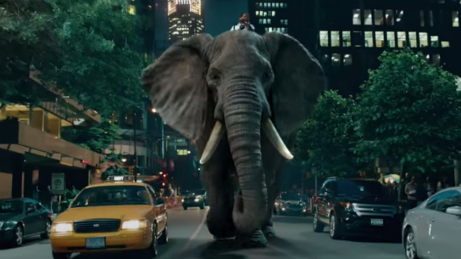 A man rides an elephant down a city street.