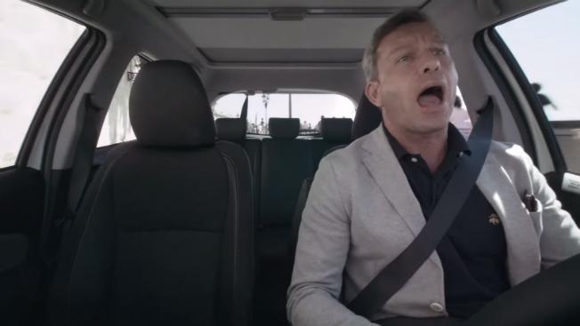 A man sings while driving a car.