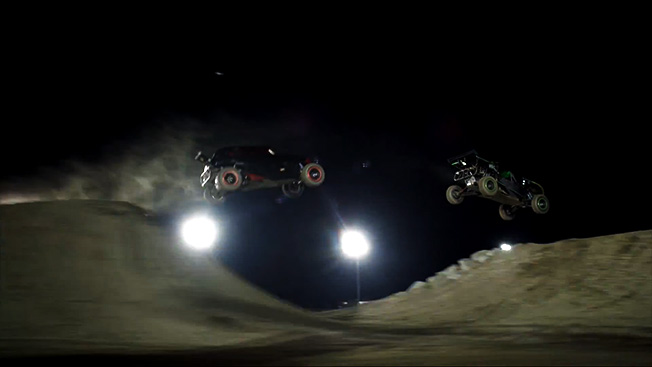 Two cars jump from ramps in a still from a Hot Wheels Ad.