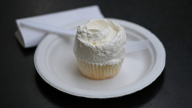 A white vanilla cupcake on a white plate with a white plastic fork and white napkin.